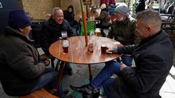 Pelanggan menikmati minuman di meja luar setelah pub Half Moon kembali dibuka di London, Inggris, Senin (12/4/2021). Inggris melonggarkan pembatasan terkait virus corona COVID-19. (Photo by Niklas HALLE'N/AFP)
