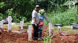 Peziarah berdiri di sisi makam korban yang diduga terinfeksi virus COVID-19 di TPU Pondok Ranggon, Jakarta, Minggu (24/5/2020). Berdasar data yang diumumkan pemerintah per 24 Mei 2020, 22.271 orang positif Corona, 1.372 meninggal dunia dan 5.402 dinyatakan sembuh. (Liputan6.com/Helmi Fithriansyah)