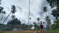 Seorang warga beraktivitas di dekat  infrastruktur jaringan 4G USO yang dikelola XL Axiata di Desa Mekar Jaya, Bunguran Barat, Natuna. (Ist.)