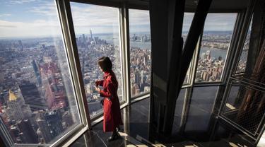 Seorang wanita menikmati pemandangan Kota Manhattan dari ruangan observatorium di lantai 102 Gedung Empire State yang baru direnovasi di New York (10/10/2019). Dibuka untuk umum pada 12 Oktober, ruang observatorium ini berjarak 1.250 kaki di atas permukaan jalan. (AFP Photo/Drew Angerer)