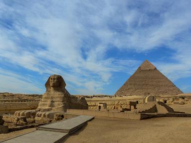 Pemandangan Sphinx dengan latar belakang Piramida Giza di pinggiran Ibukota Kairo, Mesir (6/12). Piramida ini adalah monumen yang tersisa dari Tujuh Keajaiban Dunia. (AFP Photo/Mohamed El-Shahed)