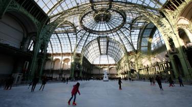 Orang-orang  berseluncur di arena ice skating di bawah kubah kaca mewah legendaris, Grand Palais, Paris, Senin (17/12). Arena ice skating musiman ini terbuka untuk umum selama liburan Natal. (AP Photo/Christophe Ena)