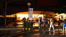 Petugas pemadam kebakaran mencoba memadamkan api di sebuah mal sesaat setelah gempa bumi bermagnitudo 6,4  melanda General Santos City, di pulau selatan Mindanao, Kamis (16/10/2019). Sekitar 100 anggota damkar dikerahkan untuk memadamkan api yang diduga akibat kebocoran gas. (EDWIN ESPEJO / AFP)