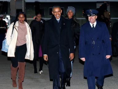 Presiden Barack Obama dan keluarga berjalan menuju pesawat Air Force One di Joint Base Andrews di Maryland, AS (16/12). Obama akan berlibur ke Hawaii untuk merayakan Natal disana. (REUTERS / Kevin Lamarque)