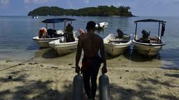 Pekerja membawa tabung oksigen isi ulang untuk scuba diving di Iboih, sebuah taman pantai dan pariwisata yang populer di seberang teluk dari Sabang di pulau Weh, provinsi Aceh (6/10/2019). Menyelam, mendaki gunung berapi dan resor pantai adalah daya tarik utama dari pulau ini. (AFP Photo/Chaideer Ma