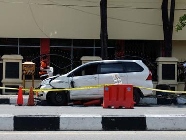 Petugas kepolisian memeriksa mobil yang digunakan terduga teroris setelah serangan di luar markas polisi di Pekanbaru, Riau (16/5). Empat pelaku penyerangan ditembak dan tewas ketika mereka melakukan serangan.  (AFP Photo/Dedy Sutisna)