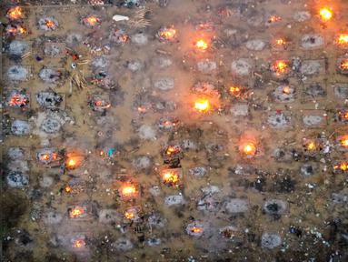 Foto dari udara memperlihatkan proses pembakaran korban yang meninggal karena virus corona COVID-19 di tempat kremasi di New Delhi, India, Senin (26/4/2021). Lonjakan kasus COVID-19 di India semakin memburuk. (Jewel SAMAD/AFP)