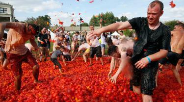 Orang-orang saling melempar tomat ketika berpartisipasi dalam festival 'Tomatina' atau perang tomat di St.Petersburg, Rusia, Minggu (18/8/2019). Tomatina atau perang tomat adalah festival Spanyol, dan tahun ini merupakan pertama kalinya dirayakan di Rusia. (AP Photo/Dmitri Lovetsky)