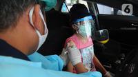Paramedis menyuntikkan vaksin COVID-19 kepada lansia saat vaksinasi secara drive-thru di ICE BSD, Tangerang, Banten, Sabtu (13/3/2021). Sebanyak 5.000 masyarakat umum, lanjut usia (lansia), dan pengemudi ojek online (ojol) divaksin COVID-19 pada hari ini dan besok. (merdeka.com/Arie Basuki)