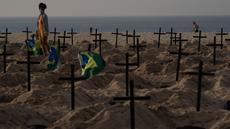 Seorang perempuan berjalan di antara ratusan kuburan di pantai Copacabana, Rio de Janeiro, Kamis (11/6/2020). Aksi simbolis yang dilakukan oleh kelompok LSM Rio de Paz itu sebagai bentuk protes atas respons pemerintah Brasil dalam menangani pandemi Covid-19. (AP Photo/Leo Correa)