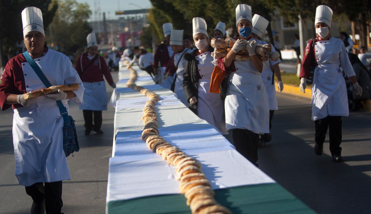 Suasana pembuatan kue raja sepanjang 2.063,43 meter di Saltillo, Negara Bagian Coahuila, Meksiko, 6 Januari 2019. Kue raja tersebut memecahkan Guinness World Record sebagai kue terpanjang di dunia. (Julio Cesar AGUILAR/AFP)