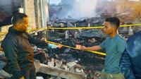 Polisi di Rokan Hilir melakukan olah tempat kejadian perkara kebakaran rumah yang menewaskan ibu dan anak. (Liputan6.com/M Syukur)