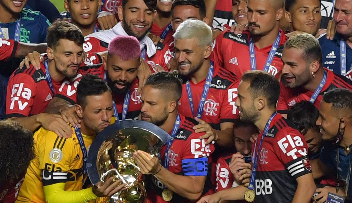 Kapten tim Flamengo Diego (kiri) mencium trofi disaksikan rekan satu timnya usai menjuarai Liga Brasil di Sao Paulo, Kamis (25/2/2021). (Foto: AFP/Nelson Almeida)