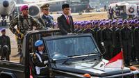 Presiden Joko Widodo menginspeksi pasukan pada perayaan HUT ke-74 TNI di Taxi Way Echo, Lanud Halim Perdanakusuma, Jakarta Timur, Sabtu (5/10/2019). HUT ke-74 TNI diikuti 6.806 personel. (Liputan6.com/JohanTallo)
