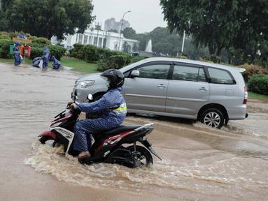 Kendaraan bermotor melintasi genangan air di Jalan Medan Merdeka Barat, Jakarta, Kamis (24/1/2020). Hujan deras yang mengguyur Jakarta sejak pagi tadi mengakibatkan genangan air di Jalan Medan Merdeka Barat. (Liputan6.com/Faizal Fanani)