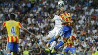 Pemain Real Madrid, Karim Benzema (kiri) atas) menyundul bola saat duel dengan pemain Valencia, Ruben Vezo pada lanjutan La Liga Spanyol di Santiago Bernabeu stadium, Madrid, (27/8/2017). Real ditahan Imbang 2-2. (AP/Francisco Seco)