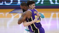 Pebasket Los Angeles Lakers, LeBron James, berpelukan dengan pemain Charlotte Hornets, LaMelo Ball. (AP/Marcio Jose Sanchez).