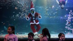 Penyelam berpakaian Sinterklas menyapa anak-anak saat tampil dalam pertunjukan bawah laut bertema Natal di Akuarium COEX, Seoul, Korea Selatan, Jumat (7/12). (Ed JONES/AFP)