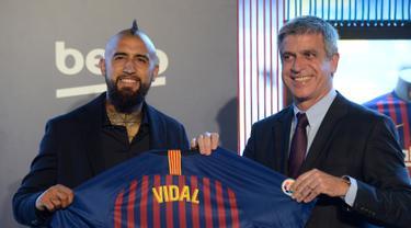 Pemain baru Barcelona, Arturo Vidal (kiri) berpose dengan Wakil Presiden Barcelona Jordi Mestre dalam presentasi resminya di Stadion Camp Nou, Barcelona, Spanyol, Senin (6/8). (Josep LAGO/AFP)