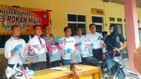 Polisi memperlihatkan barang bukti kasus pembunuhan di Polres Rokan Hilir. (Liputan6.com/M Syukur)