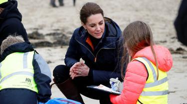 Kate Middleton, Duchess of Cambridge, berbincang dengan seorang anak sekolah saat membersihkan sampah di pantai Newborough di Wales (8/5). Pangeran William dan Kate Middleton melakukan kunjungan ke pantai Newborough untuk membersihkan sampah bersama anak-anak sekolah. (Reuters/Phil Noble)