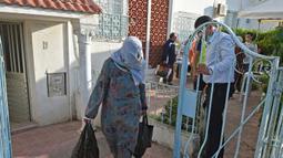 Warga membawa makanan berbuka puasa gratis dari relawan selama bulan suci Ramadan di Ariana, Tunisia (7/5/2020). Masjid-masjid di Aljazair, Maroko dan Tunisia telah ditutup untuk membatasi penyebaran Covid-19, mencegah doa malam khusus. (AFP/Fethi Belad)