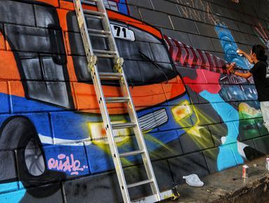 Seniman dari Komunitas mural dan Gravity membuat gambar di Kolong Tol, Jakarta, Rabu (19/6/2019). Pembuatan Mural Gravity tersebut bermaksud untuk membuat lingkungan sekitar menjadi indah dan elok dipandang mata. (Liputan6.com/Johan Tallo)