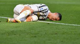 Striker Juventus, Cristiano Ronaldo, tampak meringis kesakitan saat melawan Inter Milan pada laga Liga Italia di Stadion Allianz, Sabtu (15/5/2021). Juventus menang dengan skor 3-2. (AFP/Isabella Bonotto)