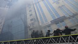 Petugas pemadam kebakaran Bangladesh menuntun orang menuruni tangga di bawah gedung kantor yang terbakar di Dhaka (28/3). Kebakaran besar melanda gedung perkantoran yang menewaskan sedikitnya lima orang dan lainnya masih terperangkap dalam gedung yang terbakar tersebut. (AFP/Munir Uzzaman)