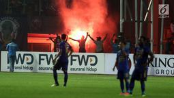Suporter tim Maung Bandung menyalakan suar saat menyaksikan laga Bhayangkara FC melawan Persib di Stadion Patriot Candrabhaga, Bekasi, Minggu (4/6). Persib kalah 0-2 dari Bhayangkara FC. (Liputan6.com/Helmi Fithriansyah)