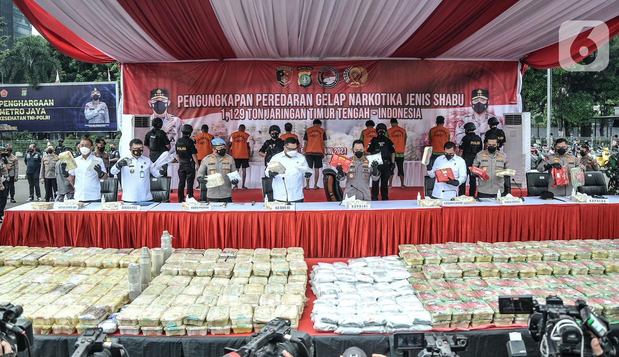 Kapolri Jenderal Listyo Sigit Prabowo (tengah) menunjukkan barang bukti saat rilis kasus narkoba jaringan Timur Tengah di Mapolda Metro Jaya, Jakarta, Senin (14/6/2021). Satgas Narkoba Polda Metro Jaya dan Polres Jakarta Pusat menggagalkan penyelundupan 1,129 ton sabu. (merdeka.com/Iqbal S. Nugroho)