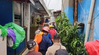 Sejumlah Petugas Gabungan Tampak Berjalan Menyusuri Pemukiman Warga dI Cipinang Melayu, Jakarta Timur. Mereka Akan Mengevakuasi Sejumlah Warga yang Terjebak Banjir di Rumahnya pada Rabu (1/1/2020). (Foto: Nanda Perdana Putra/Liputan6.com)