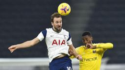 Striker Tottenham Hotspur, Harry Kane, duel udara dengan pemain Fulham, Tosin Adarabioyo, pada laga Liga Inggris di London, Rabu (13/1/2021). Kedua tim bermain imbang 1-1. (Glyn Kirk/Pool via AP)