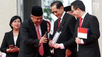 Gubernur BI Perry Warjiyo dan Presdir BCA Jahja Setiaatmadja mencoba transaksi menggunakan QR Code Indonesian Standard (QRIS) di kantor BI, Jakarta, Sabtu (17/8/2019). QRIS merupakan bagian transformasi digital di Sistem Pembayaran Indonesia yang berlaku 1 Januari 2020. (Liputan6.com/HO/Rizal)