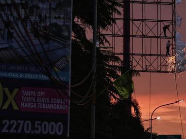 Dua pekerja memotong papan reklame yang telah tidak digunakan di kawasan Jalan TB Simatupang, Jakarta, Senin (11/2). Pemerintah Provinsi DKI Jakarta menganggarkan Rp 11 miliar untuk penertiban reklame ilegal. (Liputan6.com/Faizal Fanani)