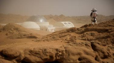 Seorang staf menggunakan pakaian astronot berada di dekat markas simulasi C-Space Project Mars yang berada di gurun Gobi, Jinchang, Provinsi Gansu, China (18/4). Kota Jinchang meningkatkan pariwisata dengan membuat para pengunjung merasa berada di planet Mars. (Reuters/Thomas Peter)