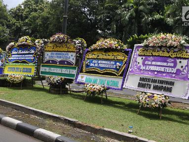 Warga mengambil gambar karangan bunga ucapan duka cita untuk Probosutedjo yang memenuhi Jalan Diponegoro, Jakarta, Senin (26/3). Probosutedjo meninggal dunia di RSCM Kencana Jakarta Pusat. (Liputan6.com/Arya Manggala)