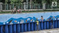 """Anak-anak bersepeda di dekat seniman yang tengah menyelesaikan pembuatan mural di turap Kanal Banjir Barat, Jakarta, Rabu (13/1/2021). Pembuatan mural ini bertemakan """"Kehidupan Sungai"""" ini dikerjakan oleh seniman dari Komunitas Mural Depok. (merdeka.com/Iqbal S. Nugroho)"""