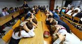 Anak-anak menutupi kepala dengan kedua tangan ketika latihan keamanan di Sekolah Nomor 8, Desa Sartana wilayah timur Ukraina, 2 Oktober 2018. Mereka mempraktikkan yang harus dilakukan jika sekolah mereka menjadi target serangan. (Aleksey FILIPPOV/AFP)