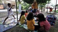 Anak-anak mengikuti program Literasi Kejujuran di TBM Saung Manggar, Pondok Kelapa, Jakarta, Minggu (24/3). Program ini bertujuan mendekatkan buku sekaligus meningkatkan minat baca kepada masyarakat dan mengurangi dampak negatif kecanduan internet bagi anak-anak. (merdeka.com/Iqbal S. Nugroho)