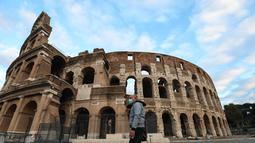 Seorang pria berjalan melewati Colosseum di Roma, Italia (4/11/2020). Museum, galeri, teater, balai konser, bioskop, dan tempat perjudian harus ditutup, sementara pertemuan publik, perayaan, pameran, festival, dan berbagai acara, baik outdoor maupun indoor, dilarang. (Xinhua/Cheng Tingting)