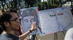 Sejumlah tanda tangan masyarakat dilukisan capres 01 yang bertema ' Pemilu Penuh Cinta'  saat Car Free day di kawasan Bundaran HI, Jakarta, MInggu (14/4). Kampanye tersebut untuk mengajak masyarakat untuk berpartisipasi dalam Pemilu secara Damai. (Liputan6.com/Faizal Fanani)