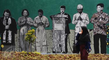 Warga melintas di depan gambar pemimpin agama di Lapangan Kebagusan, Jakarta, Rabu (15/2). Jelang menggunakan hak pilihnya pada Pilkada, Ketua Umum PDI-P Megawati Soekarnoputri menggoreskan tinta pada salah satu gambar. (Liputan6.com/Helmi Fithriansyah)