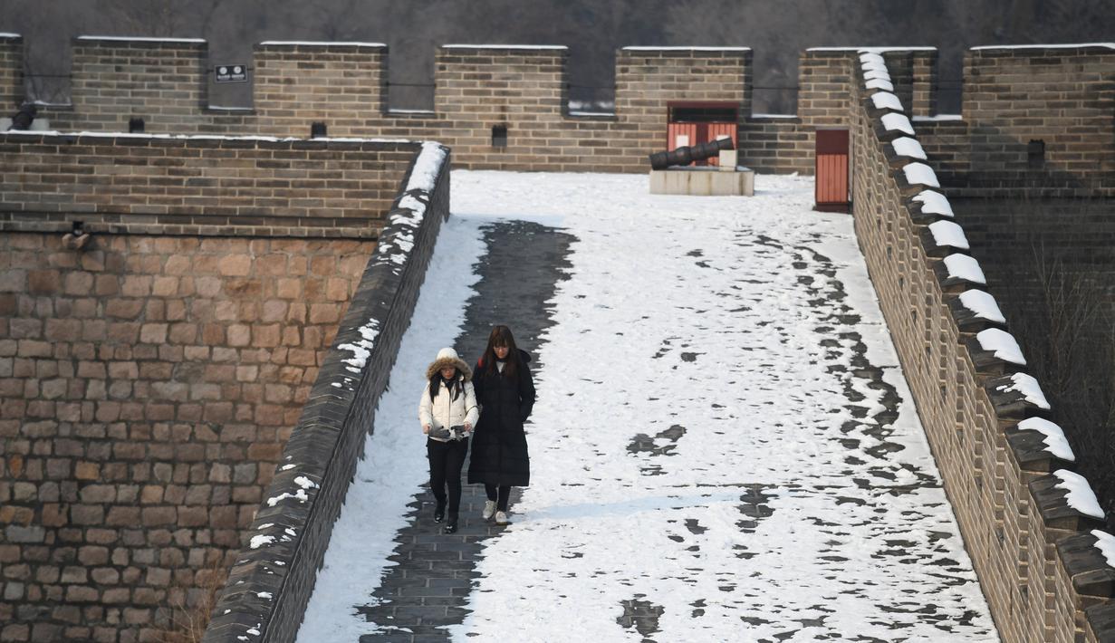 Dua wisatawan berjalan usai hujan salju mengguyur Tembok Besar China di utara Beijing (6/1/2020). Awal tahun 2020, musim dingin turun menyelimuti bagian utara Beijing yang mengakibatkan lokasi wisata yang menjadi salah satu keajaiban dunia tertutup salju. (AFP/Greg Baker)