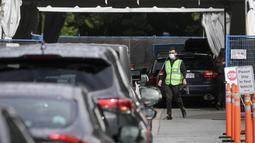 Seorang staf mengatur lalu lintas di luar sebuah pusat pengujian COVID-19 di Vancouver, British Columbia, Kanada (24/9/2020). Jumlah kasus COVID-19 melonjak secara nasional di Kanada, dari sekitar 300 kasus baru harian pada pertengahan Agustus menjadi 1.248 pada Selasa (22/9). (Xinhua/Liang Sen)