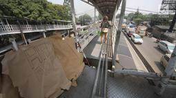 Pejalan kaki sebelum melewati lubang di atas JPO di Halte Bus Transjakarta di Jembatan Gantung, Cengkareng, Jakarta, Jumat (27/7). JPO yang rusak akibat tertabrak truk sejak setahun lalu hingga kini belum diperbaiki.  (Liputan6.com/Arya Manggala)