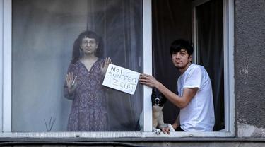 "Anak-anak muda memegang kertas bertuliskan ""kami dalam isolasi"" sambil menyaksikan protes pembatasan terkait pandemi COVID-19 di Bucharest, Rumania, Senin (29/3/2021). Ribuan pengunjuk rasa antipembatasan turun ke jalan sehari setelah langkah pembatasan baru diberlakukan. (AP Photo/Vadim Ghirda)"