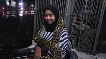 Pritta saat berteduh dari hujan di daerah Kecamatan Kalitidu, Kabupaten Bojonegoro, mengalungkan ular piton di tubuhnya. (Liputan6.com/Ahmad Adirin)