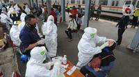 Paramedis mengambil sampel penumpang KRL Commuter Line saat tes swab di Stasiun Bojonggeder, Jawa Barat, Senin (11/05/2020).  Tes swab dan rapid dilakaukan sebagai salah satu metode untuk mendeteksi dan mencegah penyebaran Covid-19 di moda transportasi KRL Commuter Line. (merdeka.com/Arie Basuki)