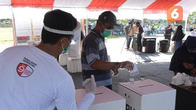 Simulasi protokol kesehatan dalam pemungutan suara yang digelar KPU Sulteng dan KPUD Palu di Lapangan Vatulemo, Sabtu (21/11/2020). Simulasi digelar untuk memantapkan kesiapan petugas dan pemilih sebelum tanggal 9 Desember 2020. (Foto: <a href=
